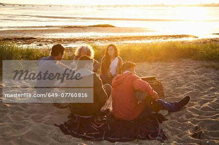 Adult friends picnicing at sunset on Bournemouth beach, Dorset, UK