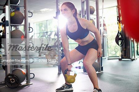 Young woman lifting kettlebell