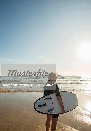 Senior female surfer standing on beach with surfboard, Camaret-sur-mer, Brittany, France