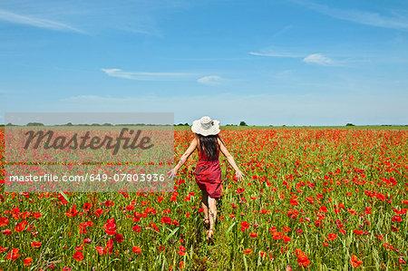 Woman walking through poppy field