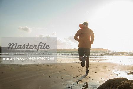 Mature man running on sand, along coastline