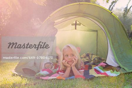 Portrait of girl lying gazing from garden tent