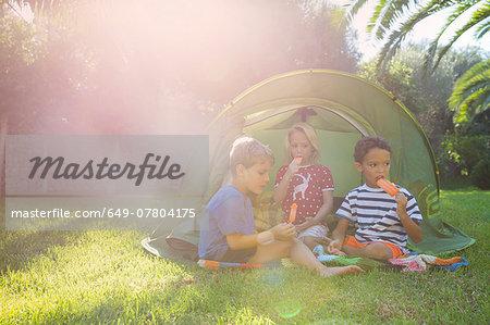 Three children eating ice lollies in garden tent