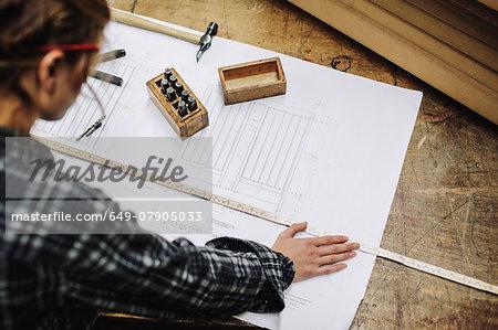 Young craftswoman measuring blueprint in pipe organ workshop