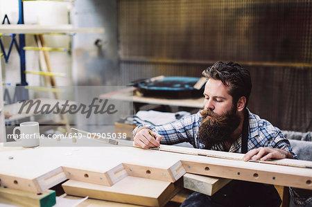 Cropped shot of mid adult craftsman measuring wood component in organ workshop