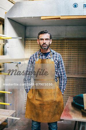 Portrait of mature craftsman in organ workshop