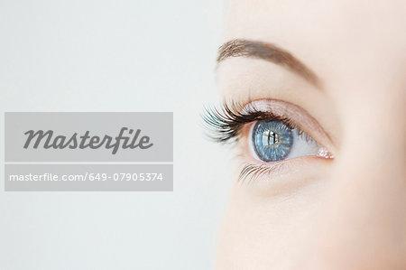 Studio close up of mid adult womans gazing blue eye