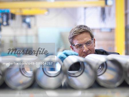 Engineer inspecting steel parts in factory