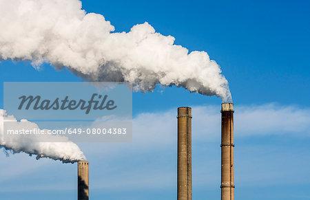 Top of smoke stacks with blue sky