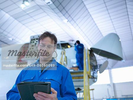Engineer using digital tablet in aircraft maintenance factory