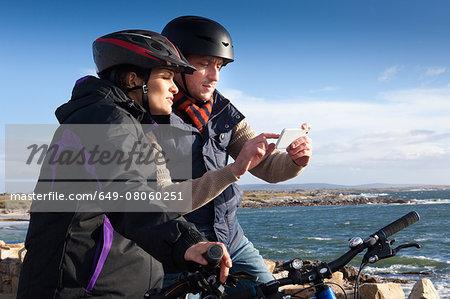 Cyclist couple using smartphone, Connemara, Ireland