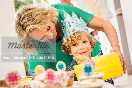 Portrait of grandmother handing birthday present to grandson