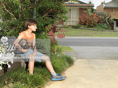 Sullen boy sitting on suburban wall holding soccer ball