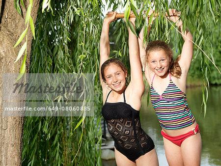 Two sisters hanging on swing beside lake