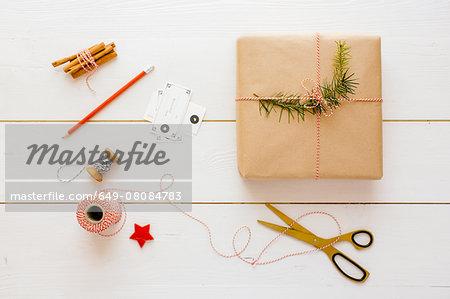 Christmas gift, thread, scissors, cinnamon sticks, pencil, labels, pine needles