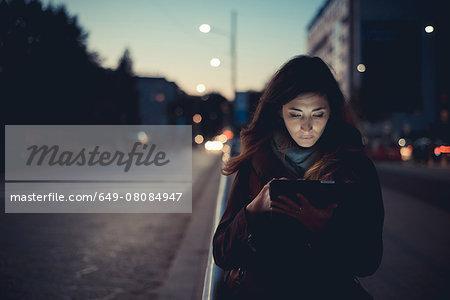 Mid adult woman using digital tablet on street at dusk