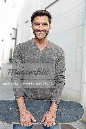 Portrait of mature man holding skateboard on sidewalk
