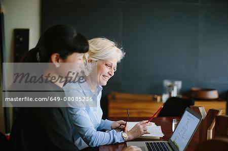 Two mature businesswomen having informal office meeting