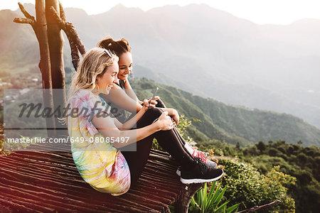 Two young female friends on balcony over Lake Atitlan, Guatemala