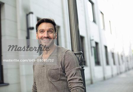 Portrait of mature man leaning against lamppost