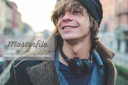 Man with headphones hung around neck