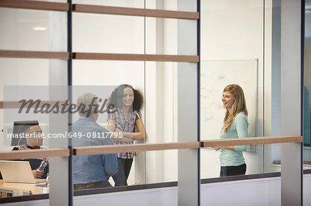 Businesswoman making team presentation on office whiteboard