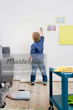 Boy drawing on wall