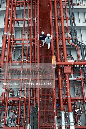 Workers walking along walkway at shipping port, elevated view, GoSeong-gun, South Korea