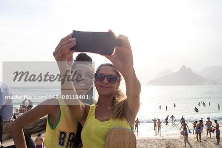 Two young women posing for smartphone selfie on Ipanema beach, Rio De Janeiro, Brazil