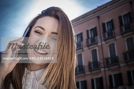 Young woman in street talking on smartphone, Cagliari, Sardinia, Italy