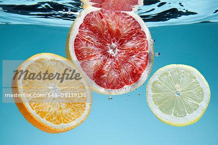 Slices of pink grapefruit, orange and lemon underwater