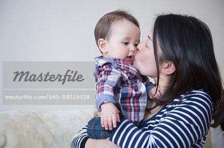 Mother kissing baby boy on cheek