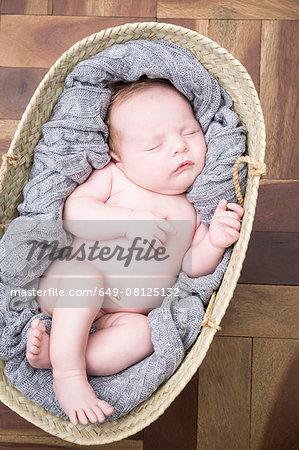 Baby sleeping snugly in moses basket