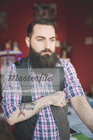 Young bearded man folding shirt sleeve