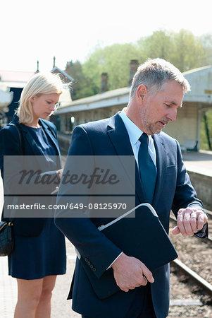 Businessman and woman checking watch on railway platform