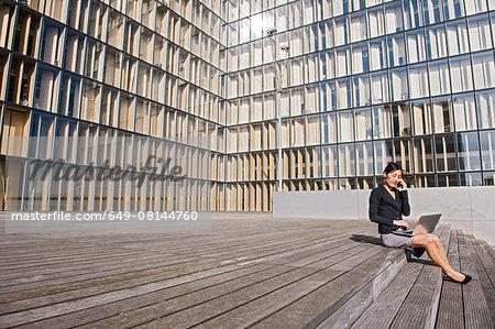Businesswoman using laptop in front of high rise building, Paris, Île-de-France, France