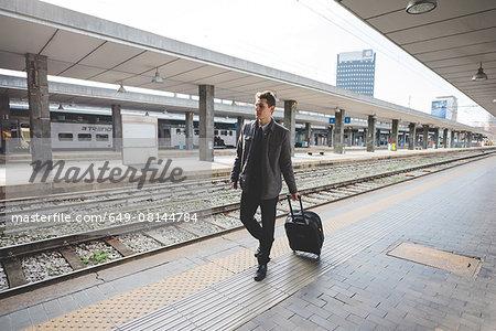 Young businessman commuter walking along train station platform pulling suitcase.