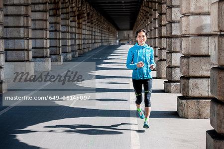 Mature female runner running in sunlit arcade