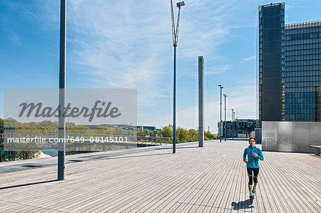 Mature female runner running along city riverside sidewalk