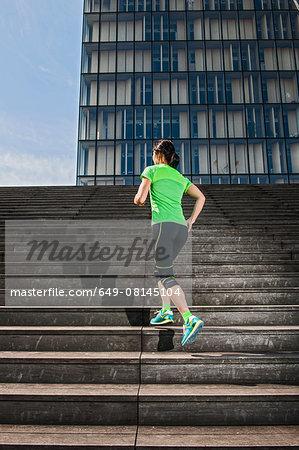 Mature female runner running up steep city stairway