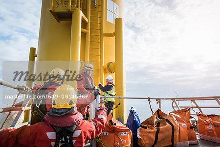 Engineers preparing to climb wind turbine on offshore windfarm