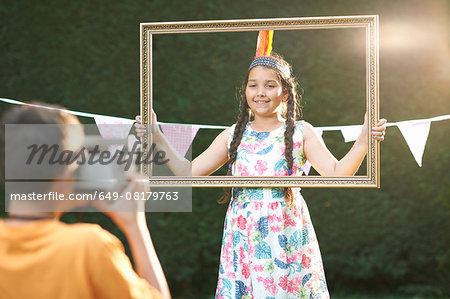 Girl looking through picture frame, having photograph taken