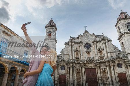 Young couple taking smartphone selfie in the Plaza de la Cathedral of Havana, Cuba