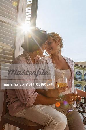 Romantic young couple drinking wine on restaurant balcony in Plaza Vieja, Havana, Cuba