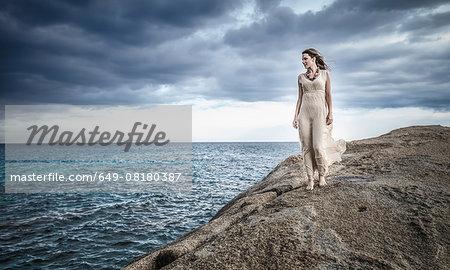 Young woman strolling along clifftop, Costa Rei, Sardinia, Italy