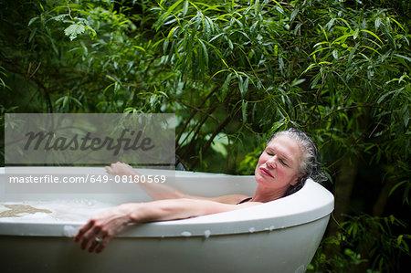 Mature woman relaxing in garden bubble bath at  eco retreat