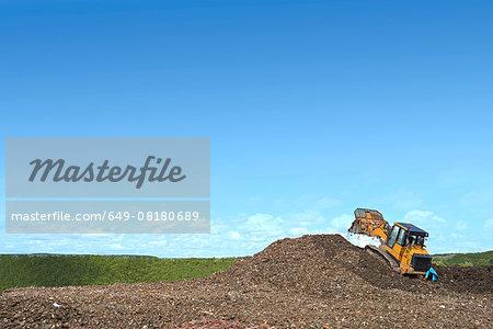 Digger on mound burying waste on landfill site