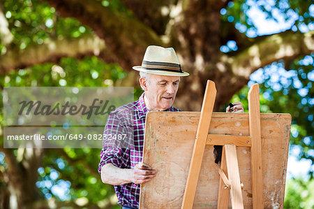Senior man drawing in park, Hackney, London