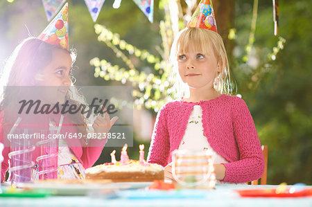 Girls with finger in birthday cake at  garden birthday party