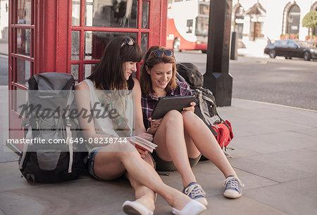 Two women backpackers sitting on sidewalk planning route on digital tablet, London, UK